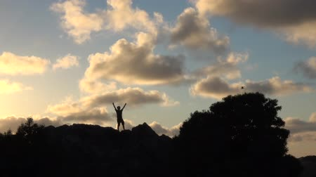 conquest : Silhouette of boy with open arms at sunset