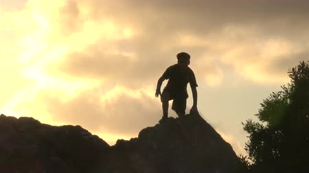 Silhouette of boy with open arms at sunset