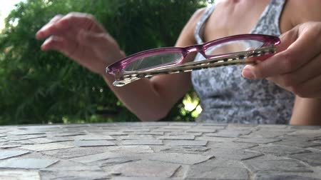 Woman putting on reading glasses Stok Video
