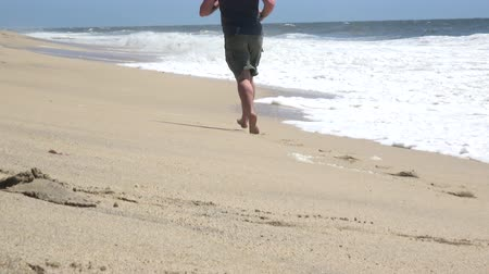Young barefoot man running on the beach