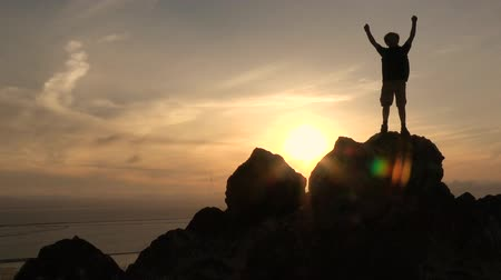 Active boy with open arms in mountains at sunset