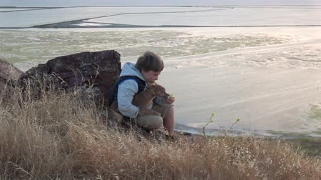 unplug : Boy sharing apple with his dog outside at sunset Stock Footage