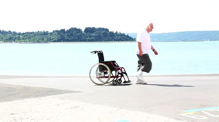 инвалидность : senior man in a wheelchair, crossing the frame from left to right. at the middle of the frame, he will stop, stand up and continue walking.