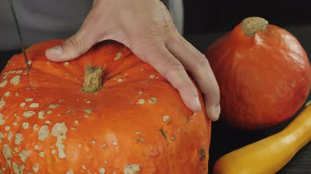 glare : Preparation for making jack-o-lantern on Halloween day. Hands begin to rotate and cut an orange pumpkin on wooden table. Close up shooting. 4K. Stock Footage