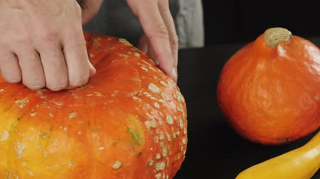 Preparation for making jack-o-lantern on Halloween day. Hand taking top off an orange pumpkin on wooden table. Close up shooting. 4K.