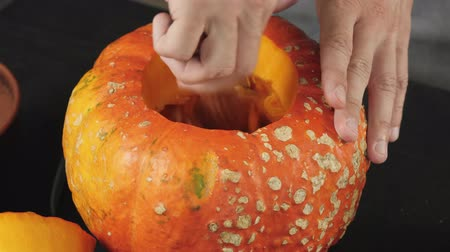 Preparation for making jack-o-lantern on Halloween day. Hand scooping pepita seeds from an orange pumpkin on wooden table. Close up shooting. 4K. 動画素材