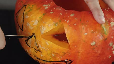 grão : Preparation for making jack-o-lantern on Halloween day. Hand cuts a hole for nose in orange pumpkin on wooden table. Close up shooting. 4K.