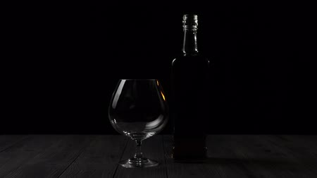 Luxury brandy. Golden cognac in a square bottle stands near a glass on a wooden table against black background. Ray of light shines on the table, glass glare in the light. Alcohol in a snifter. 4K.