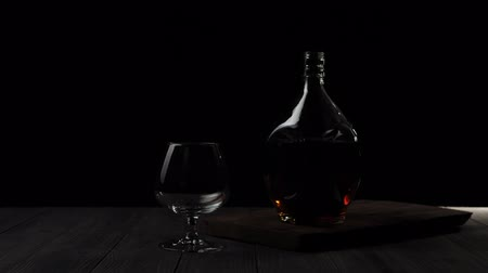kırmızı şarap : Luxury brandy. Golden cognac in a circle bottle stands near a glass on a wooden table against black background. Ray of light shines on the table, glass glare in the light. Alcohol in a snifter. 4K. Stok Video