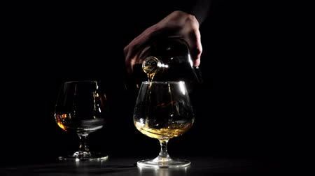 bourbon whisky : Luxury brandy. Man in a black shirt pours gold cognac from a round bottle into a glass in the foreground. Brandy, cognac, snifter, binge. Slow motion. 4K.