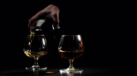 şarap kadehi : Luxury brandy. Man in a black shirt pours gold cognac from a round bottle into a glass in the background. Brandy, cognac, snifter, binge. Slow motion. 4K. Stok Video