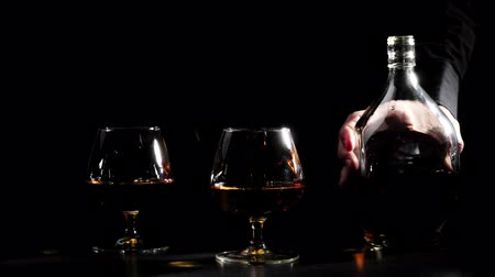 Luxury brandy. Man in a black shirt puts a round bottle of gold cognac near two glasses on black background. Brandy, cognac, snifter, binge. Slow motion. 4K.