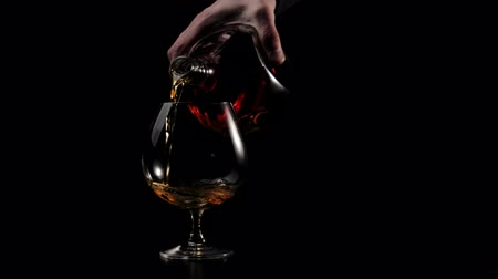 Luxury brandy. Man in a black shirt pours gold cognac from a round bottle into a glass on black background. Brandy, cognac, snifter, binge. Slow motion. 4K.