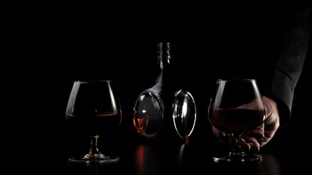 Luxury brandy. Hand takes one of two glasses with golden cognac from a black table against black background. Brandy, cognac, snifter, binge. Slow motion. 4K.