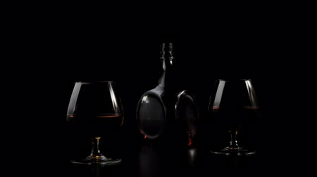 Luxury brandy. Golden cognac in a round bottle stands near two glasses on a black table against black background. Ray of light shines on the table, glass glare in the light. Alcohol in a snifter. 4K.