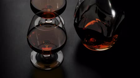 Luxury brandy. Round bottle with golden cognac and two glasses spin on black table against black background. Glass glare in the light. Brandy, cognac, snifter, binge. Slow motion. 4K.