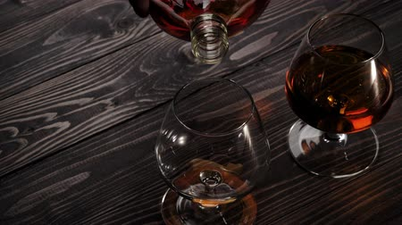 şarap kadehi : Luxury brandy. Hand takes round bottle and pours golden cognac in one of two glasses on wooden table. Brandy, cognac, snifter, binge. Slow motion. 4K.