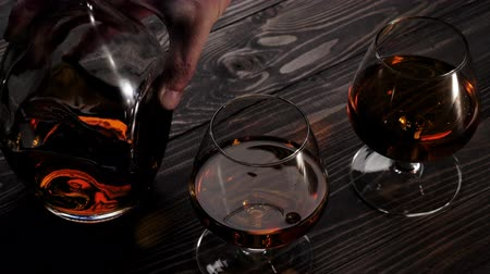 скотч : Luxury brandy. Hand puts round bottle near two glasses on wooden table. Brandy, cognac, snifter, binge. Slow motion. 4K.