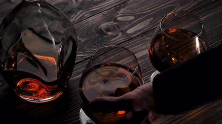 bourbon whisky : Luxury brandy. Hand puts one of two glasses from the left side on wooden table. Brandy, cognac, snifter, binge. Slow motion. 4K.
