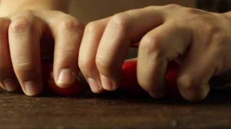 Two Hands Taking In and Out Tomato in a Wooden Surface