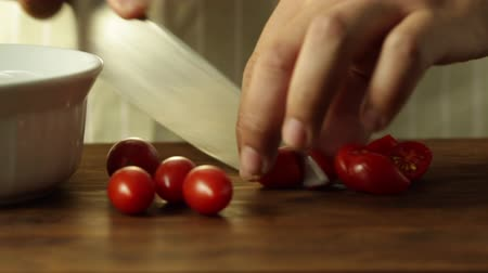 Chef Cutting Tomato Cherry Into A Bowl