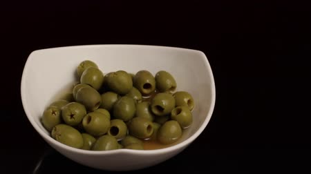 Throwing a Plate of Olives in a Black Surface