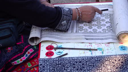 hilltribe : Close-up female hand of Hmong hilltribe draws pattern the wax on white fabric before dyeing in the countryside Thailand.4K video Stock Footage