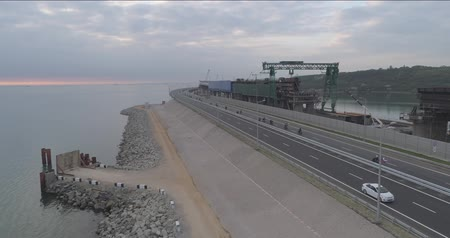krym : Taman, Russia - May 16, 2018: Fly over the drone of the Crimean bridge and the entrances to it before the opening of the traffic. The Crimean bridge. Dostupné videozáznamy