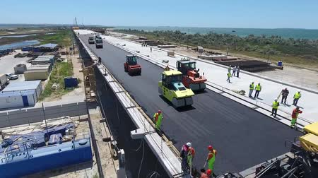 Construction of the road and paving of asphalt during the construction of the bridge. Large-scale construction of infrastructure. Wideo