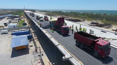 Construction of the road and paving of asphalt during the construction of the bridge. Large-scale construction of infrastructure. Dostupné videozáznamy