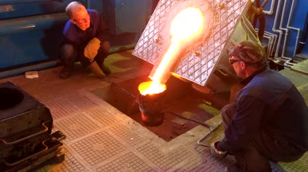 fire facilities : Saratov, Russia - November 23, 2017: Furnace for metal remelting. Pouring metal from the furnace by workers. Stock Footage
