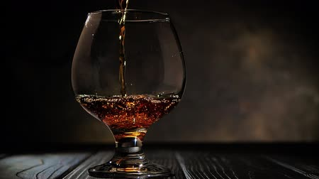 pálinka : Cognac is poured into a glass. On dark background.