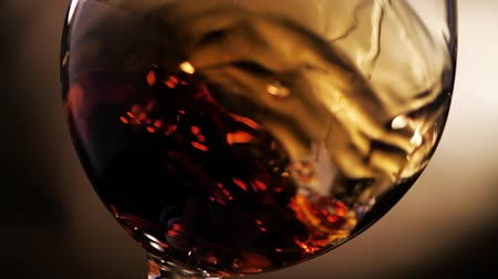 Cognac is rotated in a glass. On dark background. Stockvideo