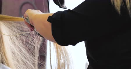 trimmer : The hairdresser dries and combs a long fair hair. Hairdressing salon. 4K UHD