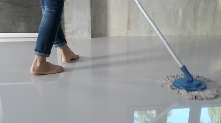 clean the house .Women work at home by rubbing the floor with a mop. Video Vídeos