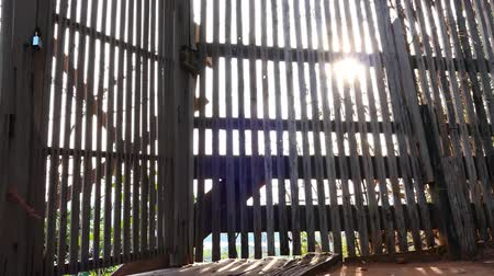 The fence is made of wood with morning sunlight. Video.