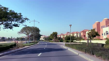 Beautiful trees and landscaping driving past the Al Badia Apartments near Dubai Festival City in the UAE 動画素材