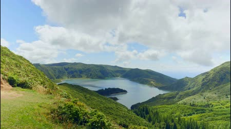 4k time lapse landscape video of lake of fire Lagoa da Fogo in Sao Miguel island Azores Portugal with clouds on blue sky moving fast projecting shadows on lagoon view in timelapse travel destination