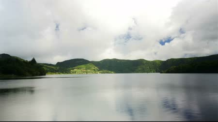 azul : 4k amazing beautiful time lapse video of Blue Lake Lagoa Azul in Sete Cidades of Sao Miguel island Azores Portugal with clouds moving fast on blue sky projecting shadows on lagoon water and mountains