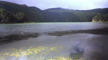 sete : 4k amazing beautiful time lapse video of Blue Lake Lagoa Azul in Sete Cidades of Sao Miguel island Azores Portugal with clouds moving fast on blue sky projecting shadows on lagoon water and mountains
