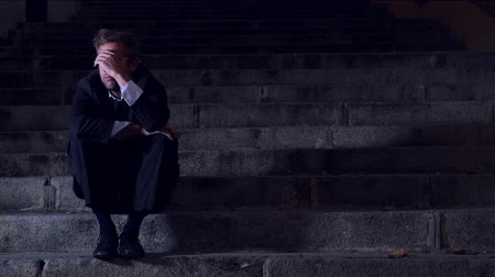 4K video lateral panning 24 fps of young desperate businessman in suit and tie suffering stress and drepression sitting on urban street staircase at night sad and worried in crisis recession concept