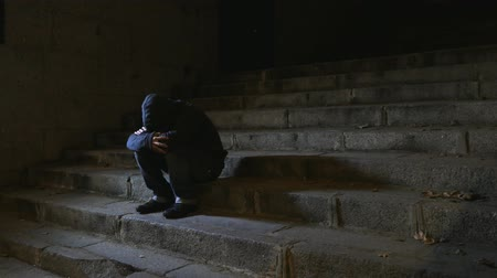 4K video lateral panning 24 fps of young desperate wasted man in hood suffering stress and drepression sitting miserable on urban street staircase at night sad and worried in addiction concept