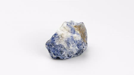 nugget : Sodalite on a white background. Mineral Rotation Decorative and ornamental stone. Nugget close up view. Jewelcrafting. Stock Footage