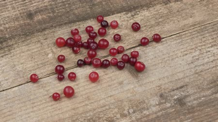 клюква : Cranberries on a wooden background. Autumn berries are scattered on old boards. Rotation Стоковые видеозаписи