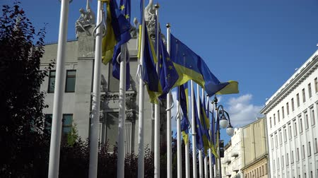 política : Two flags of Ukraine and the European Union are fluttering in the wind on the sky background. The concept of cooperation, friendship between Ukraine and the EU