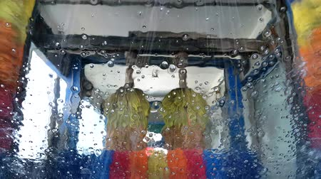 inside cars : Rotating brushes and running water with soap in a car wash, view from inside through the windscreen.
