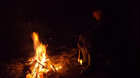 şenlik ateşi : man sitting around the campfire at night