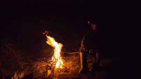 atividades : man sitting around the campfire at night