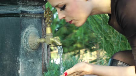 eski moda : Lady drink water from an old Fountain