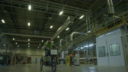 distribution lectrique : KAZAN, TATARSTAN  RUSSIA - AUGUST June 2015: Worker in uniform rides three-wheels bike along spacious plant workshop with metal pipes on August 06 in Kazan Stock Footage